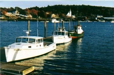 Boats at town pier and view of Our Lady Queen of Peace Catholic Church - Boothbay Harbor